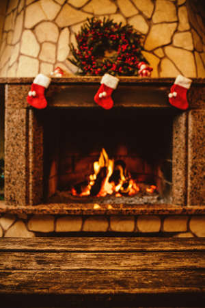 Warm cozy fireplace decorated for Christmas with real wood burning in it. Cozy Christmas concept. Christmas background with space for your text.