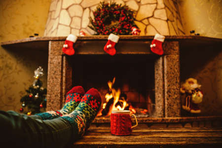 Feet in woollen socks by the Christmas fireplace. Woman relaxes by warm fire with a cup of hot drink and warming up her feet in woollen socks. Close up on feet. Winter and Christmas holidays concept. Imagens