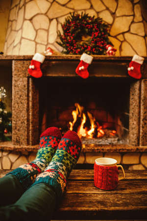 woollen: Feet in woollen socks by the Christmas fireplace. Woman relaxes by warm fire with a cup of hot drink and warming up her feet in woollen socks. Close up on feet. Winter and Christmas holidays concept. Stock Photo