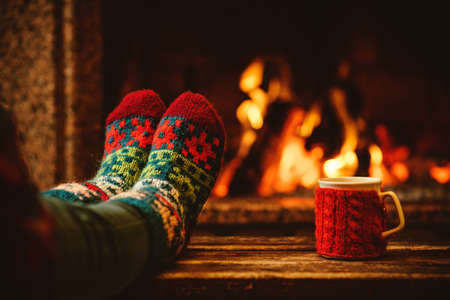 unrecognisable people: Feet in woollen socks by the Christmas fireplace. Woman relaxes by warm fire with a cup of hot drink and warming up her feet in woollen socks. Close up on feet. Winter and Christmas holidays concept. Stock Photo