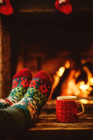 diciembre: Pies en calcetines de lana junto a la chimenea de la Navidad. La mujer se relaja por el fuego caliente con una taza de bebida caliente y calentar sus pies en calcetines de lana. Cerca de los pies. Invierno y vacaciones de Navidad concepto.