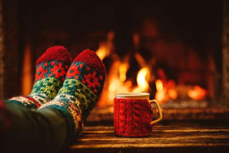 camino natale: Piedi in calzini di lana davanti al camino di Natale. La donna si distende dal fuoco caldo con una tazza di bevanda calda e riscaldamento suoi piedi in calzini di lana. Vicino a piedi. Inverno e le vacanze di Natale concetto.