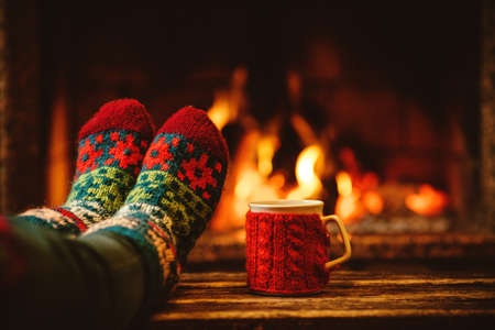 cabaña: Pies en calcetines de lana junto a la chimenea de la Navidad. La mujer se relaja por el fuego caliente con una taza de bebida caliente y calentar sus pies en calcetines de lana. Cerca de los pies. Invierno y vacaciones de Navidad concepto.