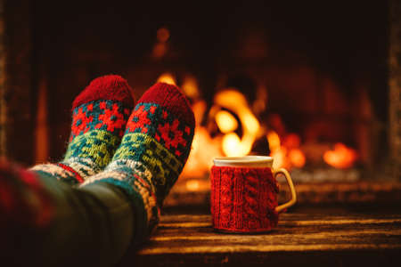 warm drink: Feet in woollen socks by the Christmas fireplace. Woman relaxes by warm fire with a cup of hot drink and warming up her feet in woollen socks. Close up on feet. Winter and Christmas holidays concept. Stock Photo