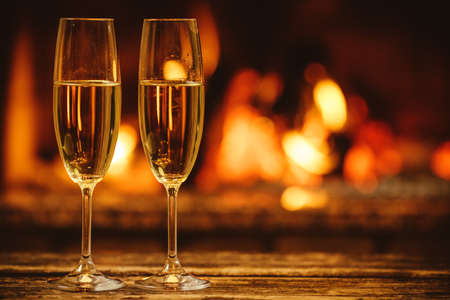 Two glasses of sparkling champagne in front of warm fireplace. Cozy relaxed magical atmosphere in a chalet house by the fireside. Snug holiday concept. Beautiful background with shimmering wine.