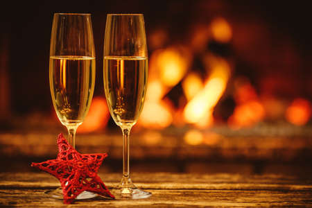 Two glasses of sparkling champagne in front of warm fireplace. Cozy relaxed magical atmosphere in a chalet. Holiday concept. Beautiful background with shimmering wine, decorated with red star.