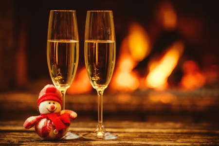 wine background: Two glasses of sparkling champagne in front of warm fireplace. Cozy relaxed magical atmosphere in a chalet. Holiday concept. Beautiful background with shimmering wine, decorated with snowman toy. Stock Photo