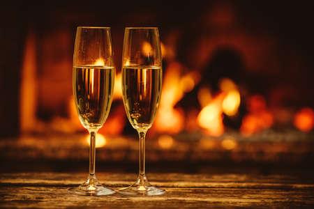Deux verres de champagne pétillant en face de foyer chaleureux. Atmosphère magique chaleureuse et détendue dans une maison chalet au coin du feu. Concept de vacances douillette. Beau fond avec du vin chatoyante. Banque d'images