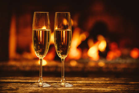 Zwei Gläser Champagner vor der warmen Kamin. Cozy entspannt magische Atmosphäre in einem Chalet Haus am Kamin. Gemütliche Ferienkonzept. Schöner Hintergrund mit schimmernden Wein. Standard-Bild