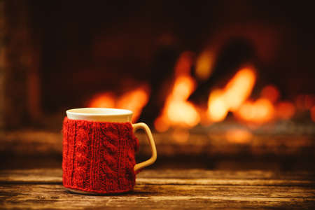 romantic places: Cup of hot drink in front of warm fireplace. Holiday Christmas concept. Mug in red knitted mitten standing near fireside. Cozy relaxed magical atmosphere in a chalet.