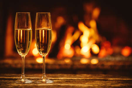 romantic places: Two glasses of sparkling champagne in front of warm fireplace. Cozy relaxed magical atmosphere in a chalet house by the fireside. Snug holiday concept. Beautiful background with shimmering wine.