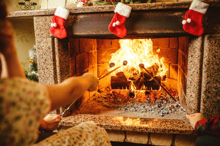 chalet: Family roasting marshmallows by the fire. Cozy chalet home with fireplace decorated with traditional Christmas ornaments. Cozy relaxed magical atmosphere in a chalet. Holiday concept.