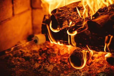 incendio casa: Asar malvaviscos por el fuego. Acogedora casa chalet con chimenea decorada con adornos navideños tradicionales. Acogedor ambiente mágico relajado en un chalet. Concepto de vacaciones.