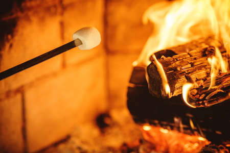 camino natale: Marshmallows torrefazione dal fuoco. Casa accogliente chalet con camino decorato con ornamenti tradizionali di Natale. Accogliente magica atmosfera rilassata in uno chalet. Concetto di vacanza.
