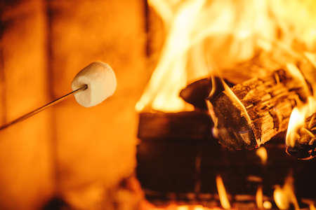 Roasting marshmallows by the fire. Cozy chalet home with fireplace decorated with traditional Christmas ornaments. Cozy relaxed magical atmosphere in a chalet. Holiday concept. 스톡 콘텐츠