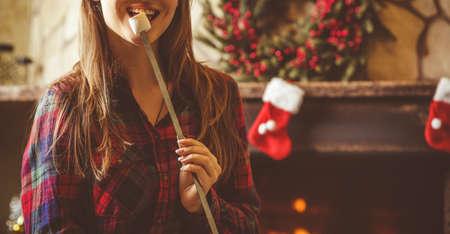 relajado: Mujer con malvaviscos junto a la chimenea. Mujer joven sonriendo y comiendo malvaviscos asados ??por la c�lida chimenea decorada para Navidad. Relajado concepto noche de fiesta. Foto de archivo