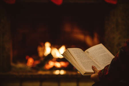 Woman reading a book by the fireplace. Young woman reading a book by the warm fireplace decorated for Christmas. Relaxed holiday evening concept. Stock Photo
