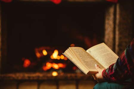 libros antiguos: Mujer leyendo un libro junto a la chimenea. Joven mujer leyendo un libro junto a la cálida chimenea decorada para Navidad. Relajado concepto noche de fiesta. Foto de archivo
