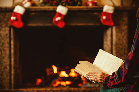 christmas fireplace: Woman reading a book by the fireplace. Young woman reading a book by the warm fireplace decorated for Christmas. Relaxed holiday evening concept. Stock Photo