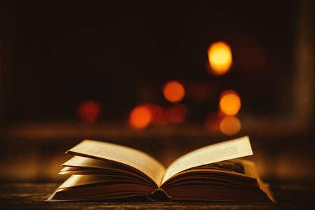 libro abierto: Abra el libro por la chimenea con adornos de Navidad. Abrir libro de cuentos que miente en un banco de madera junto a la chimenea. Acogedor ambiente mágico relajada en una casa chalet decorado para la Navidad. Concepto de vacaciones.