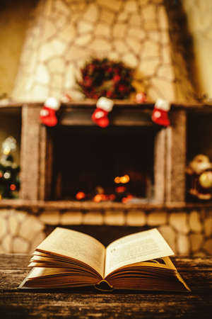 storybook: Open book by the Fireplace with Christmas ornaments. Open storybook lying on a wooden bench by the fireside. Cozy relaxed magical atmosphere in a chalet house decorated for Christmas. Holiday concept. Stock Photo