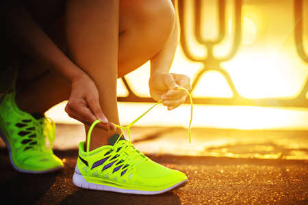 sport: Running shoes. Barefoot running shoes closeup. Female athlete tying laces for jogging on road in minimalistic barefoot running shoes. Runner getting ready for training. Sport lifestyle. Stock Photo