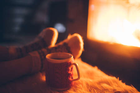 Woman relaxes by warm fire with a cup of hot drink and warming up her feet in woolen socks.