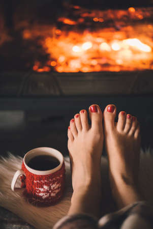 Woman relaxes by warm fire with a cup of hot drink and warming up her feet. 스톡 콘텐츠