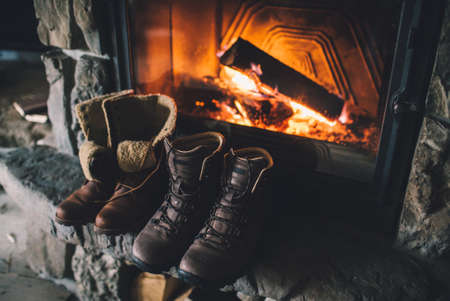 vacation home: Winter boots in front of a fireplace.