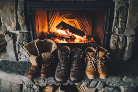Winter boots in front of a fireplace.