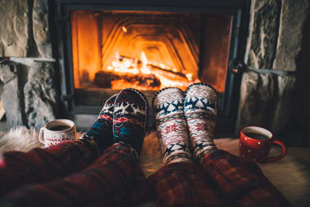 Couple sitting under the blanket, relaxes by warm fire and warming up their feet in woolen socks. Standard-Bild