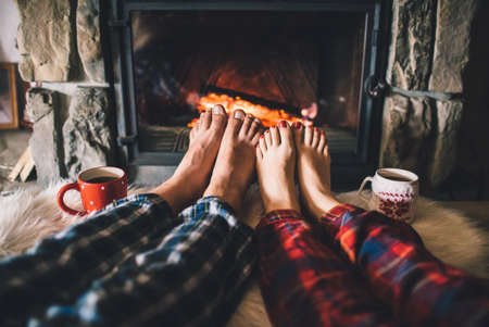 Man and Woman relaxes by warm fire with a cup of hot drink and warming up her feet.