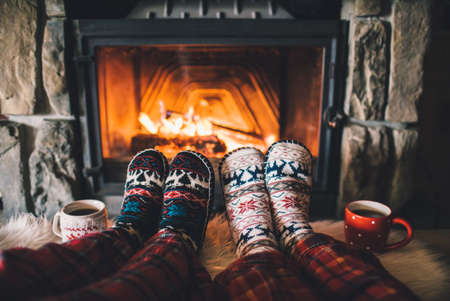 under fire: Couple sitting under the blanket, relaxes by warm fire and warming up their feet in woolen socks. Foto de archivo