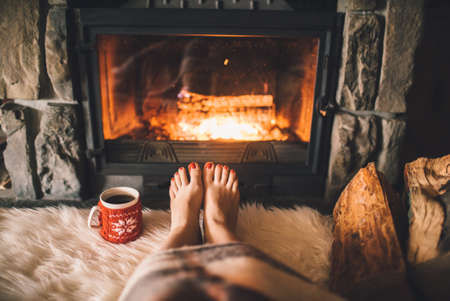 chalets: Woman relaxes by warm fire with a cup of hot drink and warming up her feet. Stock Photo