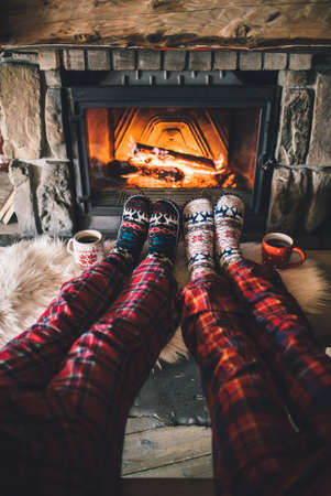 Couple sitting under the blanket, relaxes by warm fire and warming up their feet in woolen socks. Imagens