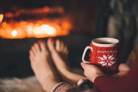 warm drink: Woman relaxes by warm fire with a cup of hot drink and warming up her feet. Stock Photo