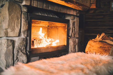 Warm cozy fireplace with real wood burning in it. Cozy winter concept. Christmas and travel background with space for your text. Stock Photo