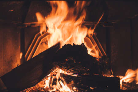 fire brick: Warm cozy burning fire in a brick fireplace close up. Cozy background