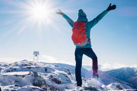 offset view: Hiker woman standing with hands up achieving the top, admiring winter mountain landscape.