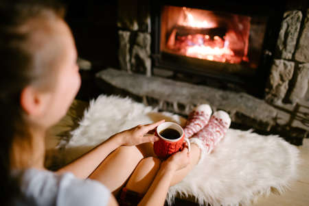 logs: Woman relaxes by warm fire with a cup of hot drink and warming up her feet in woolen socks.