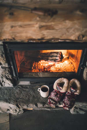 comfortable: Christmas comfortable slippers by the warm cozy fireplace. Stock Photo