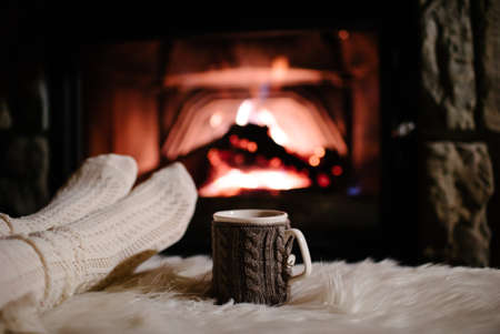 unrecognisable person: Woman relaxes by warm fire with a cup of hot drink and warming up her feet in woolen socks.