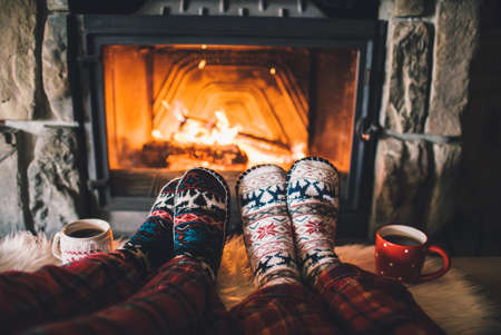 Stopy w skarpetkach wełnianych przy kominku Bożego Narodzenia. Para siedzi pod kocem, relaksuje przez ciepłego ognia i rozgrzewa nogi w wełnianych skarpetkach. Zima i Boże Narodzenie święta koncepcji.