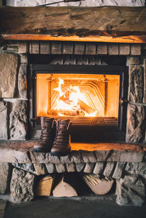 logs: Winter boots in front of a fireplace.