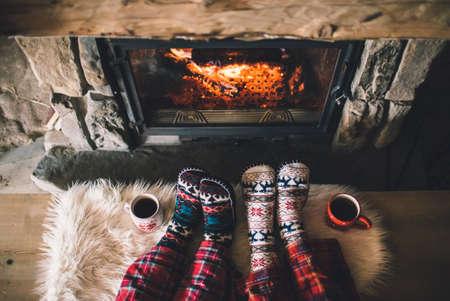 under fire: Pareja sentada debajo de la manta, se relaja por el fuego caliente y calientan sus pies en los calcetines de lana.