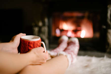 woollen: Woman holding a cup of tea by the Christmas fireplace. Woman relaxes by warm fire with a cup of hot drink and warming up her feet in woollen socks. Close up on feet. Winter, Christmas holidays concept