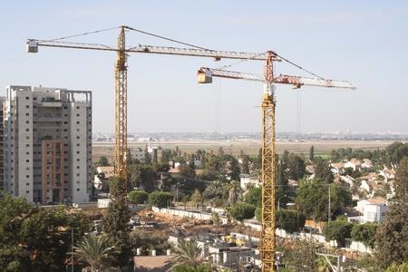 2 gru a torre costruire l'edificio pi� alto della citt�. costruzione su uno sfondo di verde aeroporto