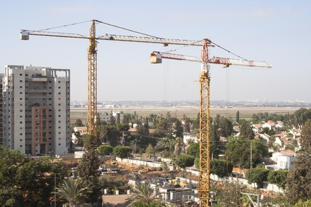 2 tower cranes build tallest building in the city. building on a background of green airport Stock Photo