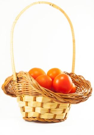 Pomodori di ciliegia in un cesto, isolato su bianco Archivio Fotografico