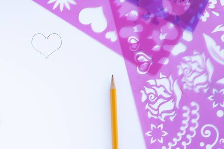 disegno su carta su un modello o stencil. Archivio Fotografico